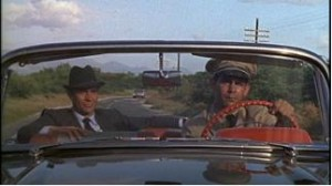Finally, in the fourth shot we see the reason for the man's haste. A second car appears behind them, and the car chase begins in earnest.