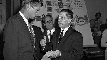 James R. Hoffa, right, Midwest boss of theTeamsters union, talks with Robert F. Kennedy, counsel for the Senate Rackets Investigating Committee in Washington, D.C., Aug. 21, 1957. Hoffa will take the witness stand for more questioning about his financial affairs. Man in rear is unidentified. (AP Photo)
